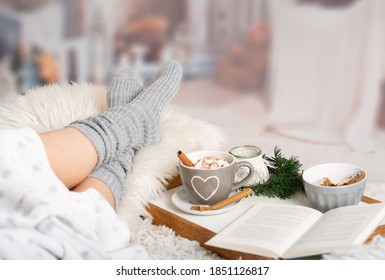Woman lies with Cup; Kako; Hot chocolate; marshmallows; Book tray; Bed; Sofa; Blanket; Snuggle blanket; Fur; Fireplace; Wind light; Indoor; Living room; Cosy; Reading; Enjoying; Relaxing; Winter time