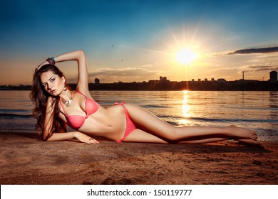 woman lies on a beach at sunset
