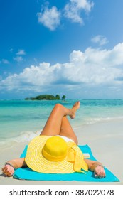 Woman lies on the beach with yellow hat and blue towel