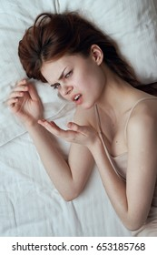 Woman lies on the bed discontent, woman nerves, woman insomnia and nerves