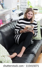 Woman lies on the couch and reads a book