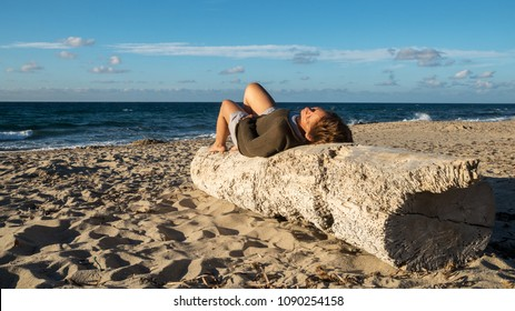 A woman lies on a log in Sardinia and enjoys the sun