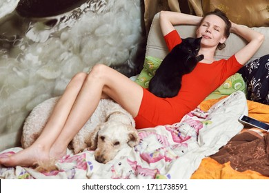 A woman lies on a sofa with a cat and a dog. Love for pets concept.