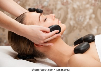 Woman lies on a table in a beauty spa getting a hot stone treatment