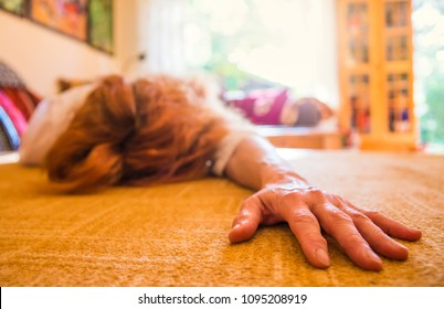 a woman lies unconscious on the carpet in a room