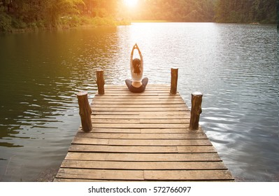 Woman lifestyle do focused yoga and peaceful outdoor. Person exercising zen yoga at the nature background.  Healthy Concept