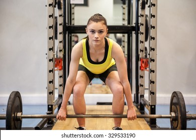 Woman lifting barbell and weights at the gym