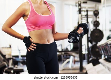 Woman lifting dumbbell with left arm. Fit woman lifting a dumbbell