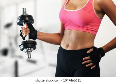 Woman lifting dumbbell with right arm. Fit woman lifting a dumbbell
