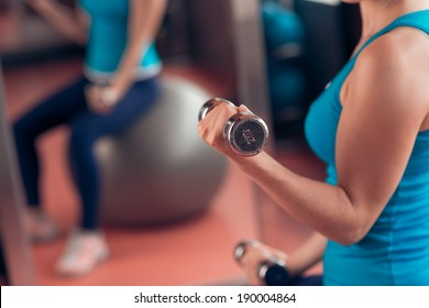 Woman lifting dumbbells in the gym