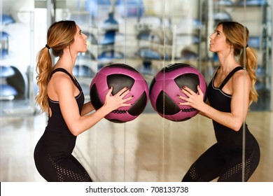 Woman lifting fitballs in the gym. Young girl wearing sportswear clothes in front of a mirror.