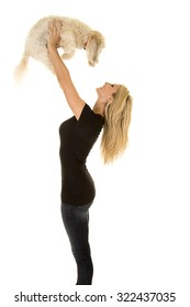 a woman lifting up her Maltese dog up over her head with a smile.