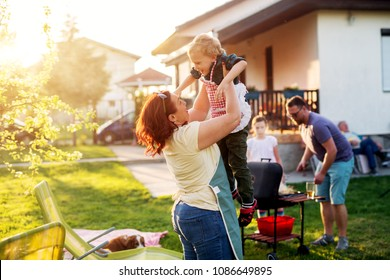 Woman is lifting up high her gorgeous and cheerful toddler boy while rest of the family is grilling.