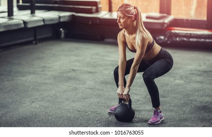 Woman lifting kettlebell at gym. Female athlete lift kettlebell on gym floor.