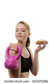 woman lifting a kettlebell weight and a cream cake