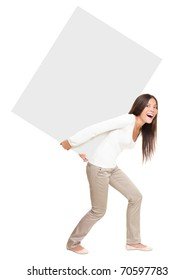 Woman lifting / showing heavy blank billboard sign. Woman carrying empty sign board on her back. Funny image of beautiful asian \ caucasian female model isolated in full length on white background.