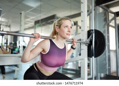 Woman lifting weight with barbell in fitness center