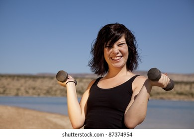 A woman lifting weights with a silly expression on her face.