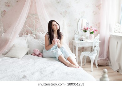 Woman in light bedroom enjoying her morning with  a cup of hot drink.