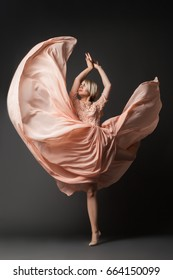 Woman in light chiffon dress dancing sensually on black plain background.