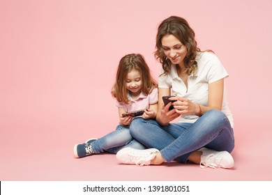 Woman in light clothes have fun with cute child baby girl. Mother, little kid daughter isolated on pastel pink wall background, studio portrait. Mother's Day love family, parenthood childhood concept