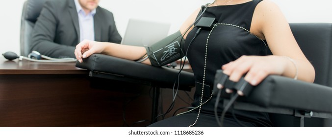 Woman with light hair, dressed in black dress - polygraph, on the table there are polygraph devices