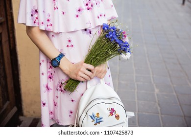 Woman in light pink dress with bouquet of cornflowers on the city streets. Stylish girl street fashion look, spring outfit. Girl with white luxury backpack and bouquet in hands
