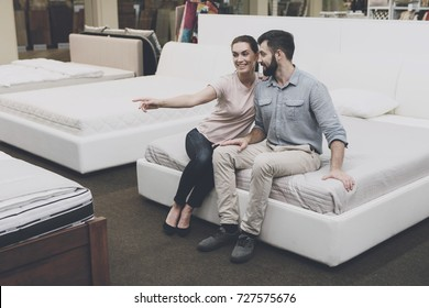 A woman in a light T-shirt and a man in a gray shirt are sitting on a bed in a bed store. A woman shows on the same bed and the neighboring beds