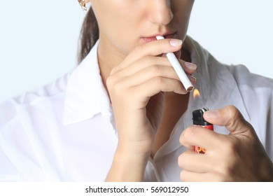 Woman lighting cigarette - studio shoot