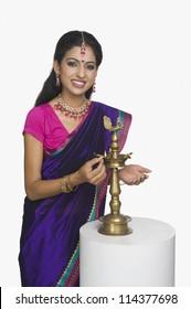 Woman lighting oil lamp