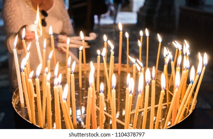 Woman lights candles in the Church of the Holy Sepulchre Jerusalem