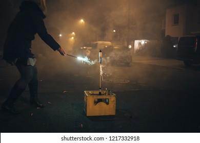 Woman lights firecracker on New Year's Eve.