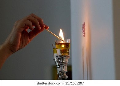 A woman lights Shabbat candles