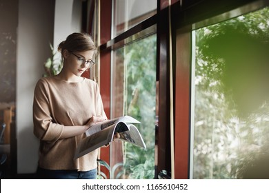 Woman likes spend time with reading. Indoor shot of cute creative and smart female in trendy outfit and glasses, holding magazine and turning pages while standing near window, taking bread from work