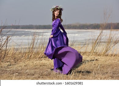 Woman lilac dress with a wreath of flowers on her head on nature in early spring