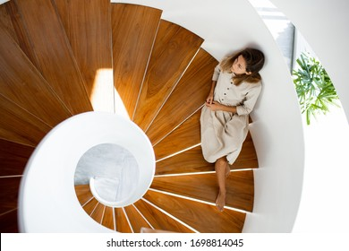 Woman in linen natural dress is sitting on the wooden modern stairs inside of the house