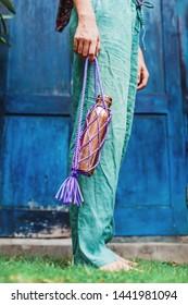 Woman in linen pants holding reusable eco-friendly copper bottle (faceless picture)