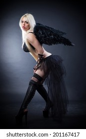 Woman in the lingerie with black angel wings against the black background
