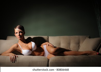 Woman in Lingerie Classic Beauty lying on a sofa with Text Space above