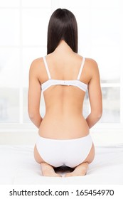 Woman in lingerie. Rear view of young woman in lingerie kneeling on the bed