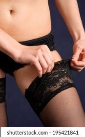 Woman in lingerie wearing black erotic stockings