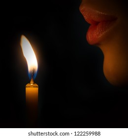 Woman lips blowing to the candle