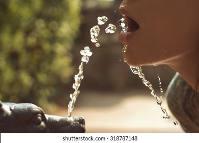 woman lips, drinking water from small fountain
