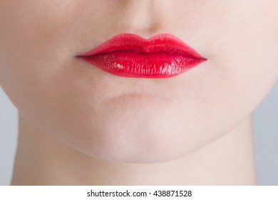 Woman lips with glossy red lipstick.