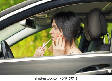 Woman with the lipstick and cell phone in the car