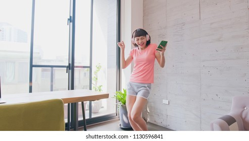 woman listen music and dance happily at home