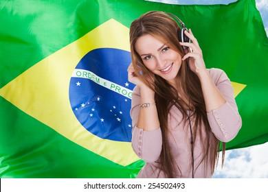 Woman Listening Brazilian Language Learning Audiobook On Headphones In Front Of Brazilian Flag