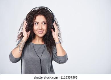 Woman listening enjoying music in headphones looking to side at blank copy space