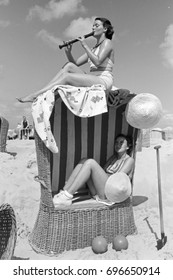 Woman listening to her friend play the flute on top of wicker chair at the beach