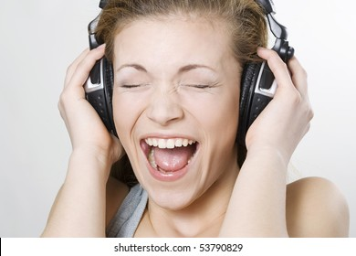 Woman listening music with big headphones and singing